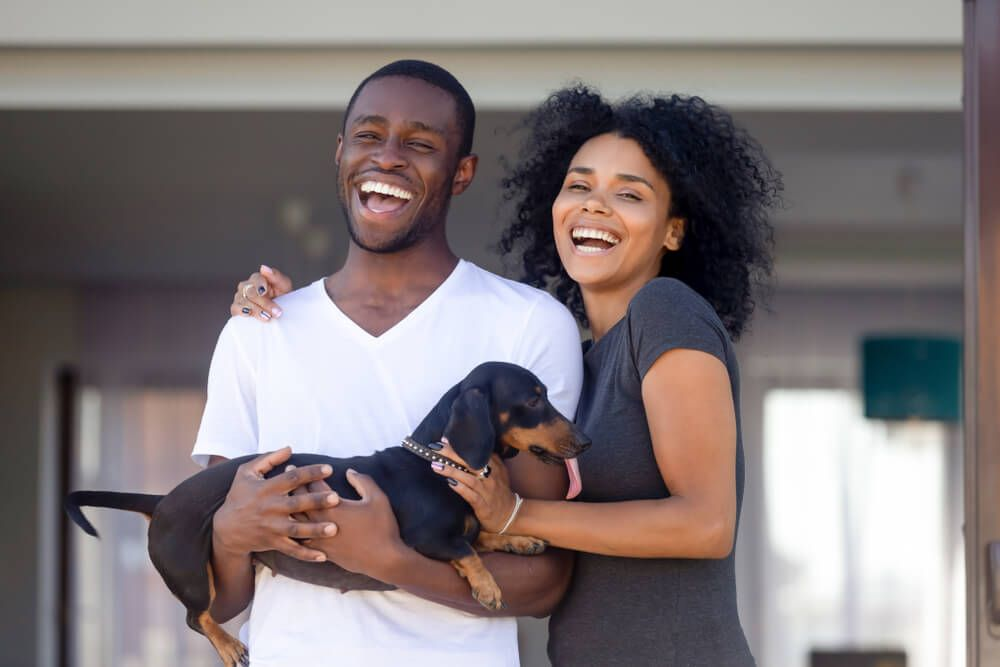 Happy-couple-stands-outside-home-with-adopted-dog