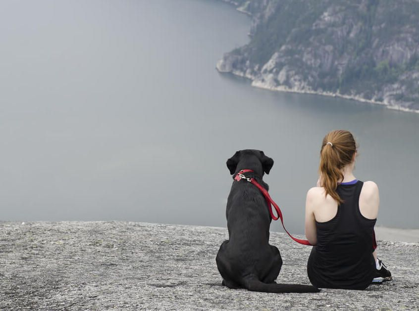 young-woman-takes-her-black-lab-on-a-long-hike