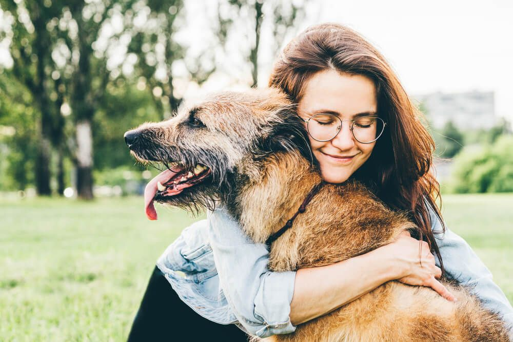 young-woman-embraces-her-aging-dog