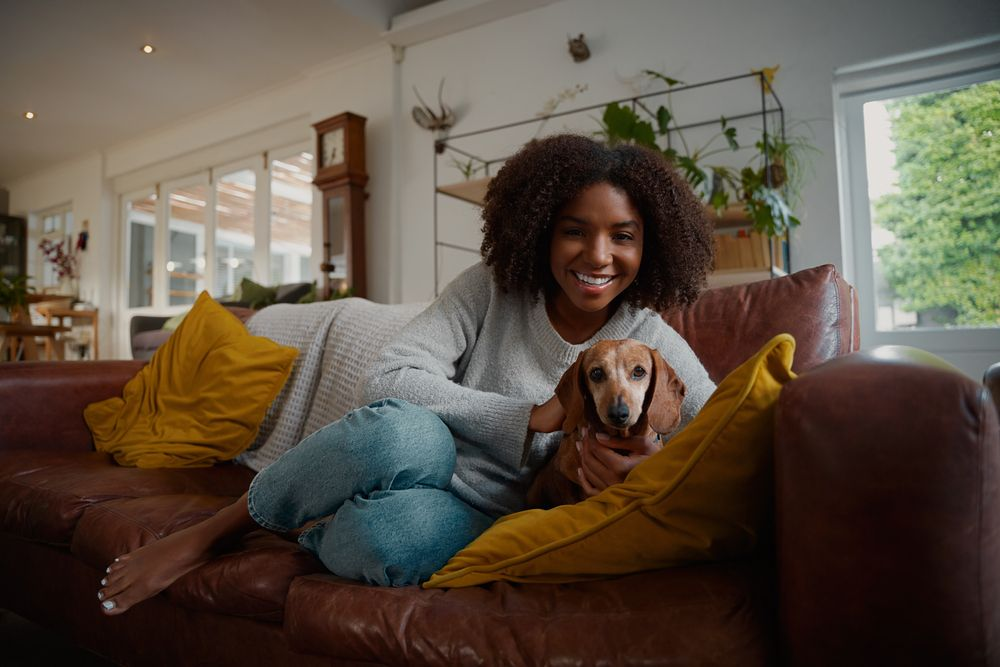 young-woman-gets-cozy-on-couch-with-dog