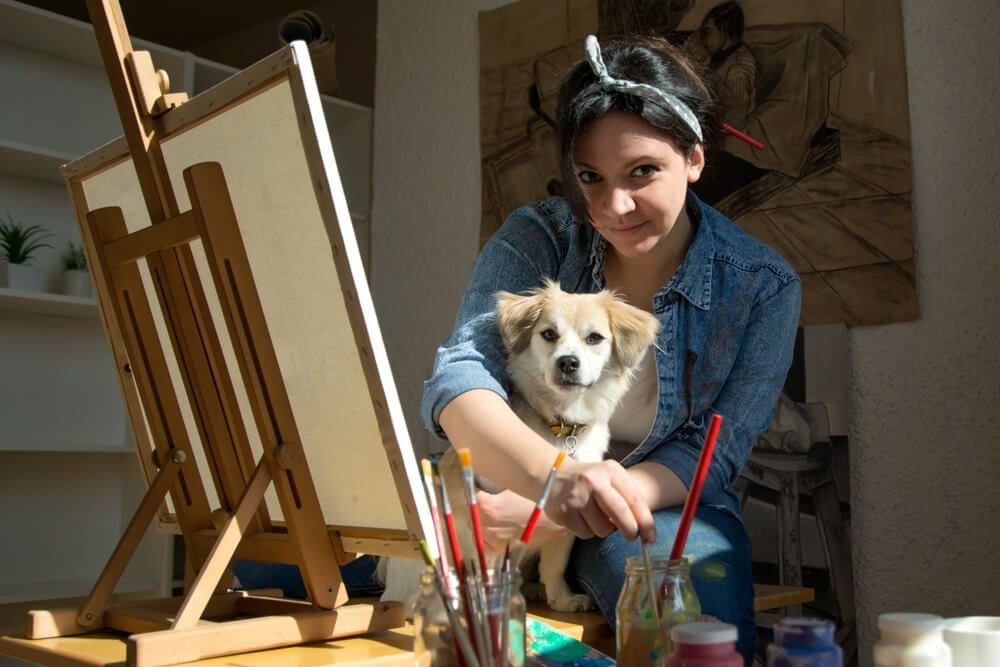 young-woman-paints-with-a-small-dog-on-her-lap