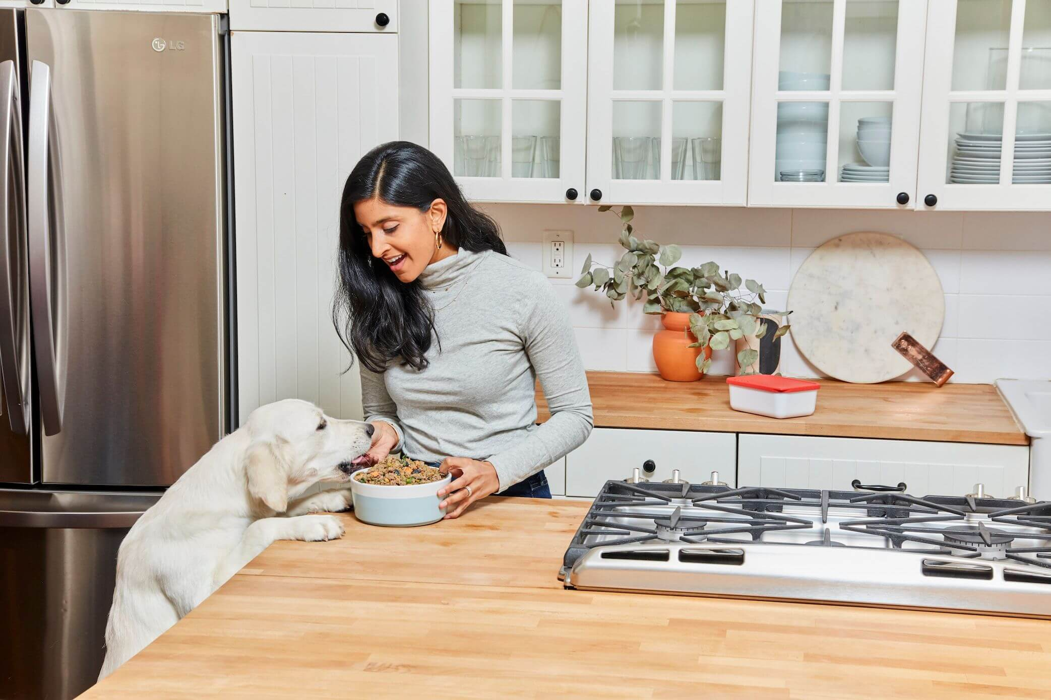 woman-feeds-her-white-dog-from-counter-in-crisp-white-kitchen--1-