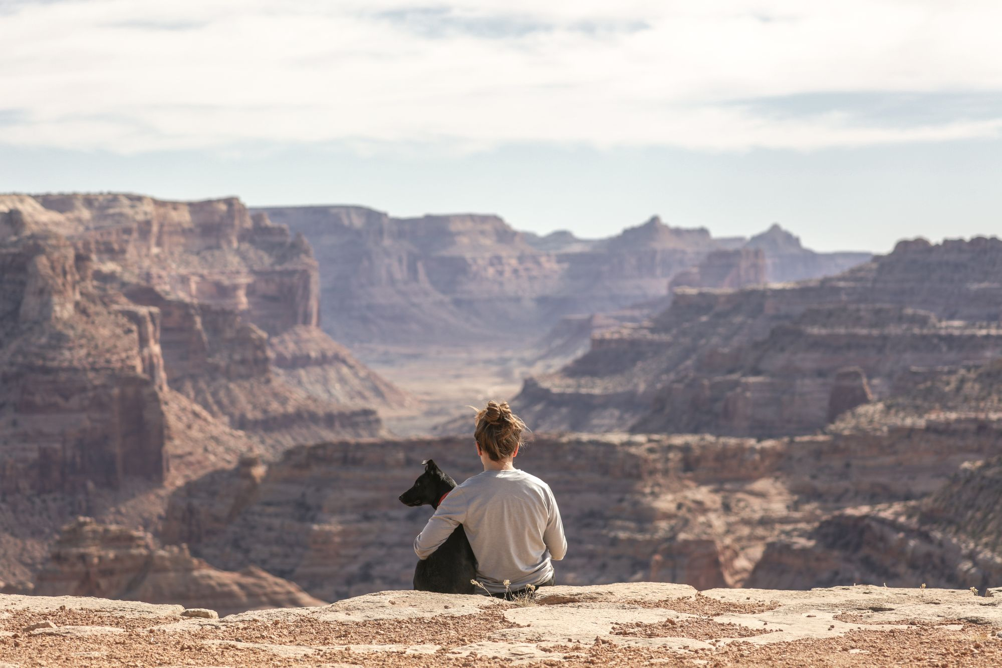 woman-with-dog-ad-the-edge-of-a-canyon-in-utah